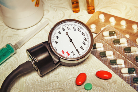 On the table is an apparatus for blood pressure measurement, which shows higher pressures. Its a hypertensive crisis. Near are medications to assist. Фото со стока