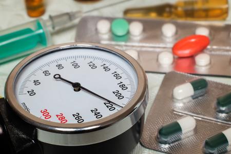 Sobre la mesa es un aparato para medir la presión arterial, lo que demuestra presiones más altas. Es una crisis hipertensiva. Cerca de medicamentos para ayudar. Foto de archivo - 59334553