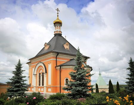 arborvitae: A beautiful Orthodox temple located on a hill surrounded by flowers and plants: arborvitae, blue spruce, shrubs.