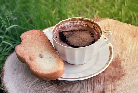 sawn: In the garden on the stump of a sawn tree trunk is a black Cup of coffee. Next on the plate are toasted white bread.