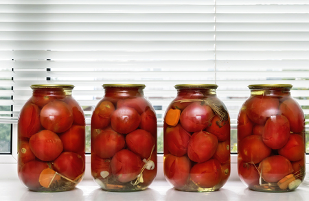 airtight: Glass jars with red ripe tomatoes, sealed airtight metal lid.