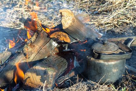 heats: In a clearing lit a fire, near which heats a kettle of water.