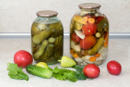 carnes y verduras: Home canning: large glass cylinders with a variety of vegetables: cabbage , tomatoes, cucumbers, peppers. Sealed with metal caps. Located next to fresh vegetables. Foto de archivo