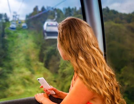 The girl in the cabin cable car into the mountains to enjoy the surrounding nature.