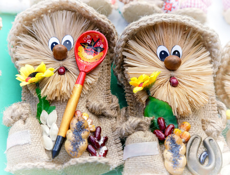 The craft: two funny dolls of cloth with symbols of wealth and prosperity. Stock Photo