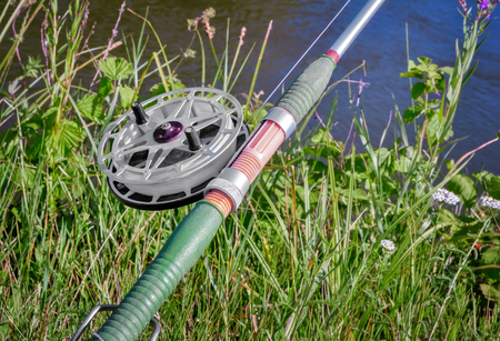 On the banks of the beautiful river over the water set fishing equipment to fish comfortably with rod and reel. Stock Photo