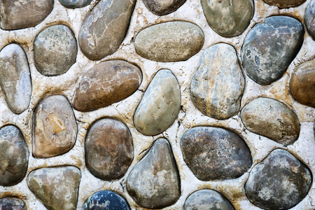 A fragment of stone wall decorated with sea pebbles of different shapes and sizes. Background image.