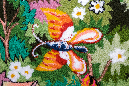 For the portion of the woven panels depict a butterfly among flowers and green leaves.