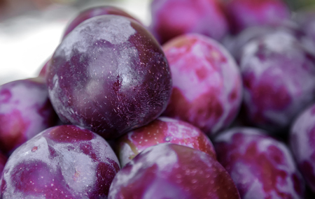 Large ripe plum fruits sold in the market. Presents close-up.