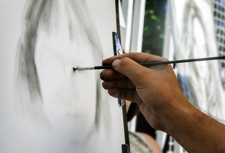 Artist on the streets draws on the easel the portrait of a woman. Stock Photo