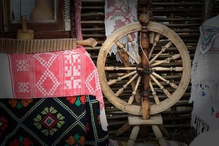 old items: Vintage wooden spinning wheels , interior items and handmade household items. Stock Photo