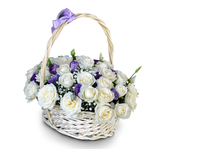 Beautiful white roses in a wicker basket decorated with ribbons. Presented on a white background. Stock Photo