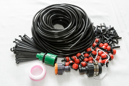 A set of tools for drip irrigation of plants and garden: hose, sprinklers, joints, hose holders.