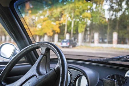 drivers seat: A fragment of the interior of the car opposite the drivers seat: steering wheel, speedometer, controls. Stock Photo