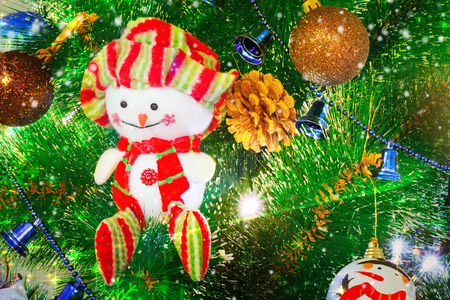Snowman in a red cap and elegant clothes against the decorated Christmas fir-tree Stock Photo