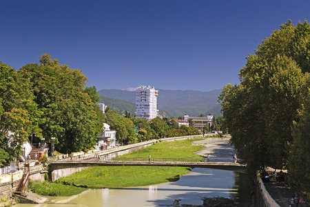 Cityscape: view of one of the streets of the resort with a mountain river and the hotels along the waterfront.