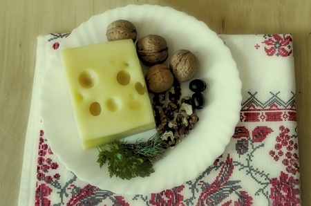 On the table on a white plate to get the cheese, walnuts and olives. The effect of the Polaroid. Stock Photo