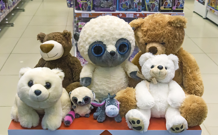baby toy: Various childrens soft toys: bear , dog and others on the storefront.