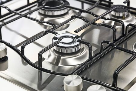 A fragment of the surface of the gas stove: burner and stand. Presents closeup. Stock Photo