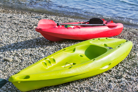 On the beach near the water there are two small single boats: red and green. Designed for walking on the sea. Reference picture.