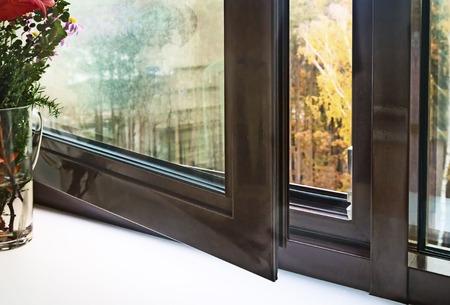 Open venster met bruine kaders en uitzicht op herfstlandschap. Stockfoto
