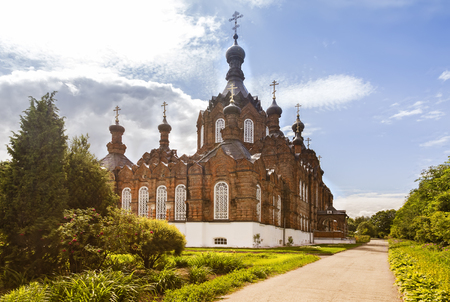 A beautiful Orthodox temple located on a hill surrounded by flowers and plants: arborvitae, blue spruce, shrubs.