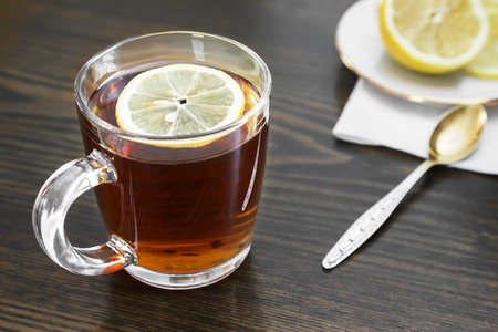 On the surface of the table in a glass Cup hot strong tea and lemon. Imagens