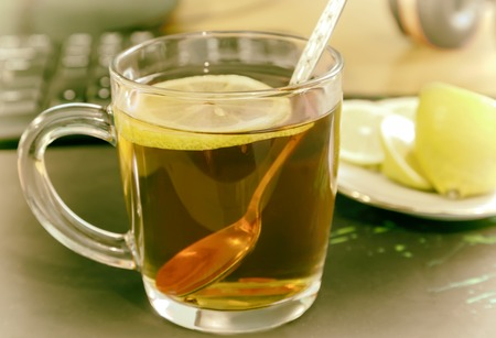 A Cup of tea and lemon on the table.
