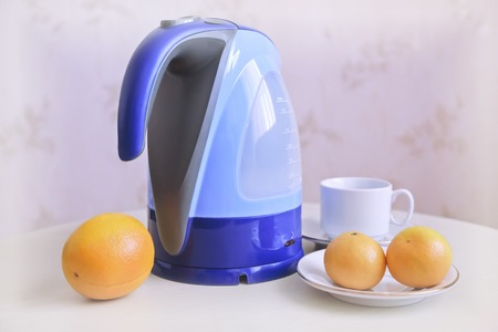 On the table is an electric kettle, next are oranges and tangerines.