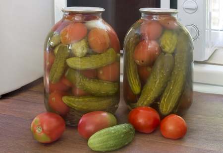 Home preservation: large glass jars with red ripe pickled tomatoes and cucumbers, sealed metal lid.
