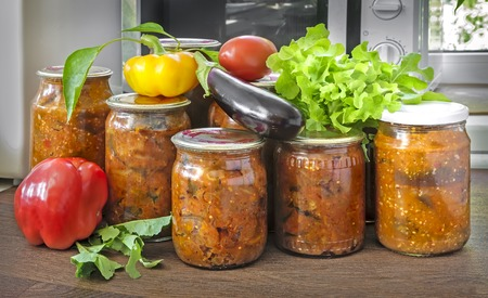 Various vegetables are preserved in glass jars with sealed metal lids: eggplants, peppers, tomatoes, onions. Fresh vegetables and green salad are nearby.