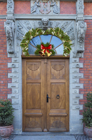 Above the beautiful wooden door hangs a Christmas wreath and bells.