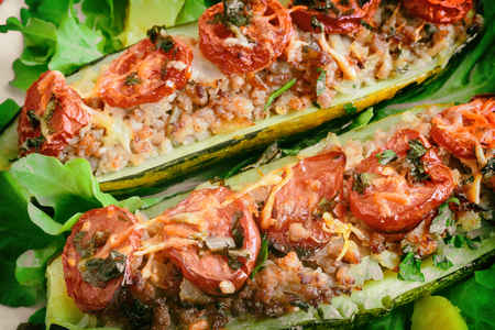 Zucchini on a plate stuffed with minced meat and vegetables with potatoes and green salad. Presented in close-up.