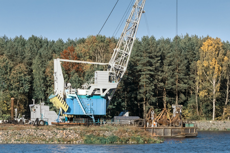 Environmental protection. On the river Bank mechanism for cleaning the river bottom and deepening the river for navigation. On the banks of the river grows thick forest. Reklamní fotografie