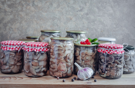 Home preservation of products: glass jars with pickled mushrooms with spices closed Stock Photo