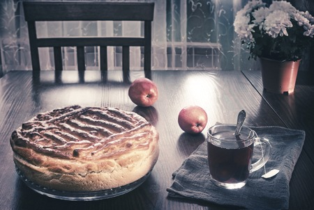 On the dining table on a glass tray is a delicious large homemade cake. On a napkin near tea in a glass and apples.