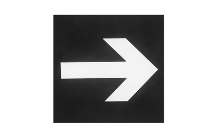 A sign on the wall with a direction indicator in the form of an arrow. Presented on a white background. Black and white image. 写真素材