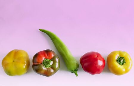 On a pink background, five Bulgarian peppers of different colors and shapes.