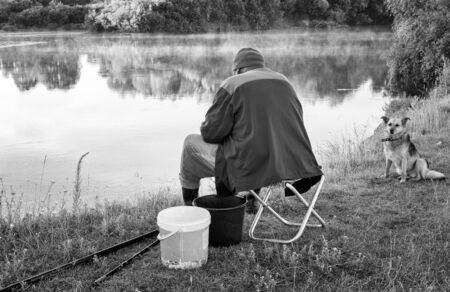 On the shore of a beautiful lake in the early morning a man fishing. Next to him sits a dog.