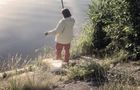 On the shore of a beautiful lake in the early morning a woman fishing. 스톡 콘텐츠