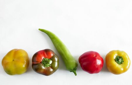 On a light background, five Bulgarian peppers of different colors and shapes. 写真素材