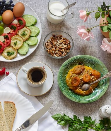Healthy Breakfast: pumpkin puree with dried apricots, muesli, kefir, vegetables, eggs, coffee. Presented on a homespun rustic tablecloth, top view. Stockfoto