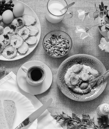 Healthy Breakfast: pumpkin puree with dried apricots, muesli, kefir, vegetables, eggs, coffee. Presented on a homespun rustic tablecloth, top view. Black and white image Stockfoto