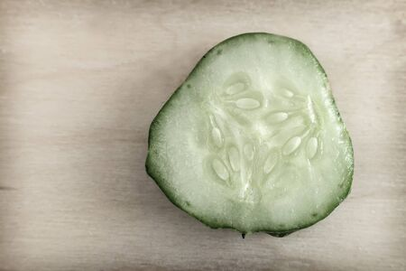 Cross-section of cucumber, top view, close-up, on a wooden background. Healthy food concept, natural product.