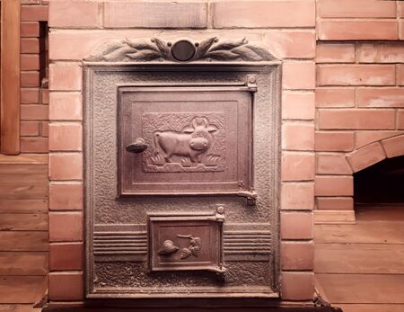 Russian bath interior: red brick stove with cast iron doors
