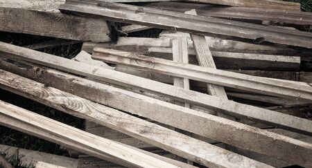 Old boards, sticks, slats piled up in a heap after repair of the premises. Intended for disposal or reuse.