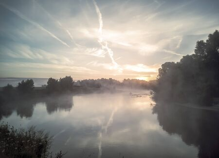 Sunrise over a small beautiful lake with fog over the water. Фото со стока