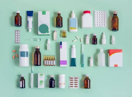 Various forms of drugs: tablets, ampoules, tinctures, blister packaging on a light green background. Place to insert text, top view. Medicine and pharmacy.