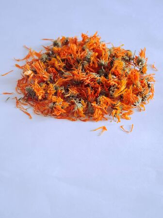 Dried calendula flowers on a light background, a drug with a bactericidal, anti-inflammatory effect. Copy space.