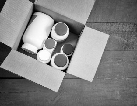 On a wooden table in a cardboard box bottles with medicines and cosmetics to send to the buyer